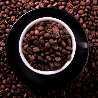 Black coffee cup filled with roasted beans top view