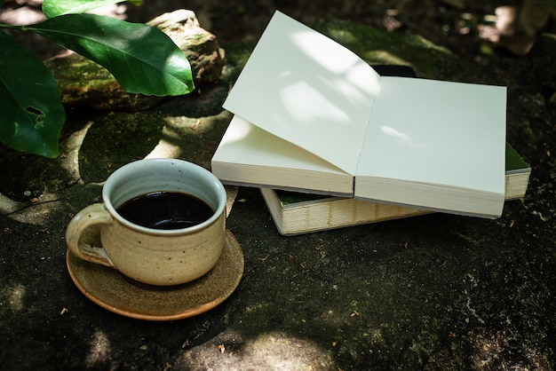 The black coffee cup put beside open book in a park