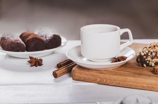 アニス、シナモン、チョコレートのお菓子が入ったブラックコーヒーカップ