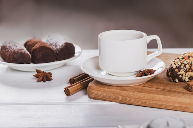 Black coffee cup with anise, cinnamon and chocolate sweets