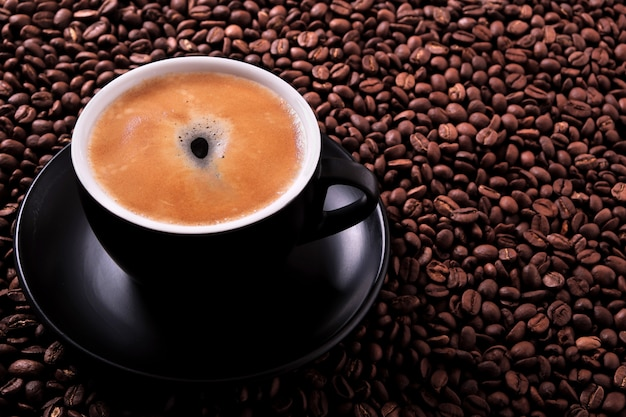 Black coffee cup with roasted beans background