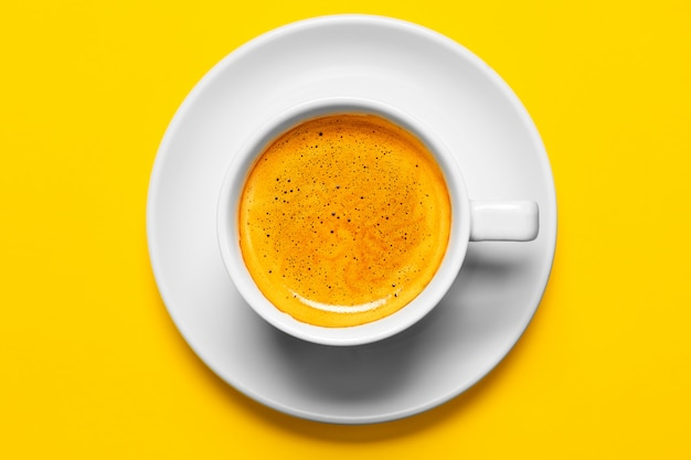 Black coffee in a cup on a yellow