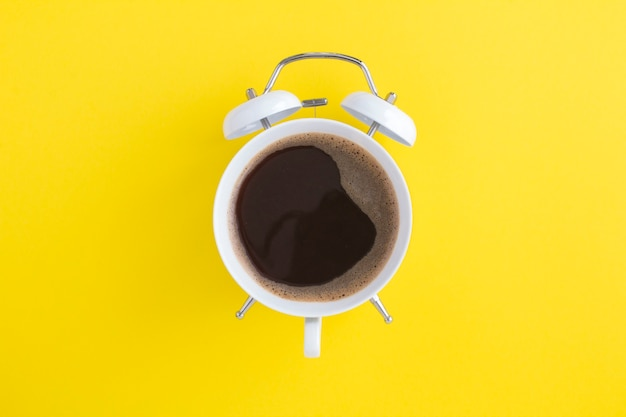 Black coffee on the dial of the white alarm clock in the center of the yellow background