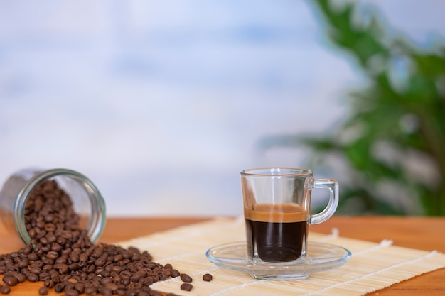 Black coffee in glass cup and coffee beans on the wooden table