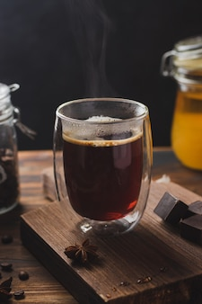 Black coffee in the glass with steam over wooden surface, honey and dark chocolate