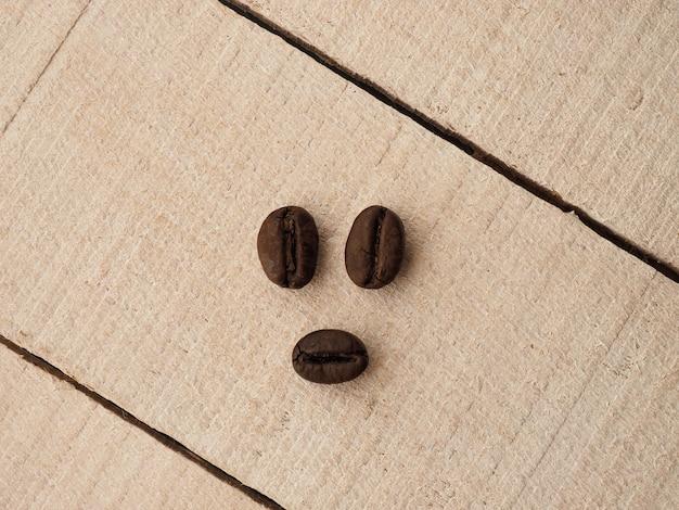 Зерна черного кофе лежат на светлом деревянном столе, фоновом изображении. место для текста