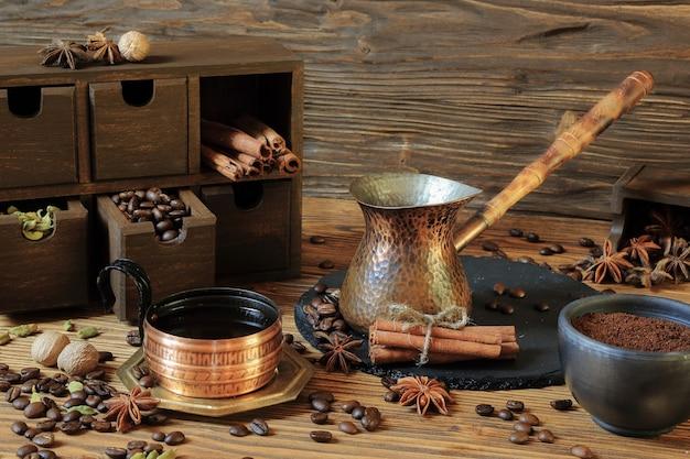 銅のカップにブラックコーヒーと木製のテーブルにスパイス