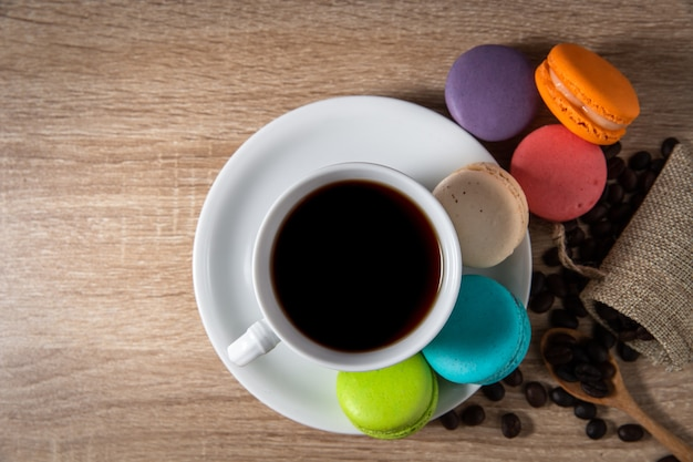 木のテーブルの背景にコーヒー豆とマカロンとカップのブラックコーヒー