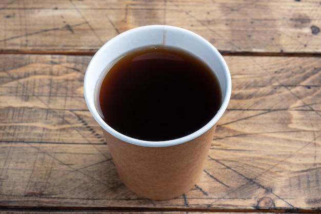木製の背景に紙コップでブラックコーヒー。フラットレイコピースペース、上面図。