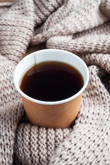 暖かい毛布の背景に紙コップでブラックコーヒー。フラットレイコピースペース、上面図。