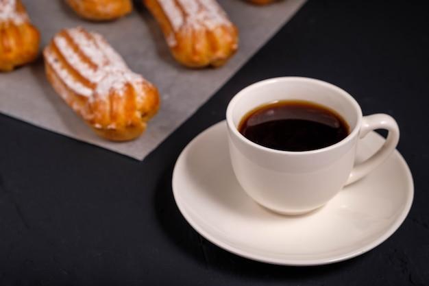 Черный кофе в белой чашке и эклеры со сливками на темном фоне