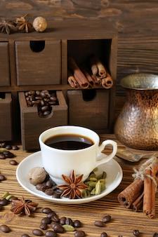 白いカップのブラックコーヒーと木製のテーブルのスパイス