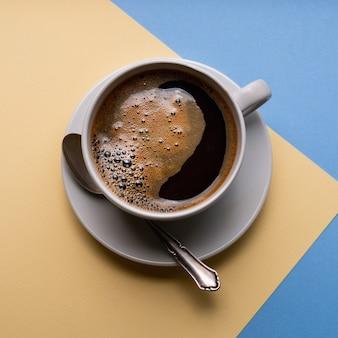 Черный кофе в белой чашке на синем и желтом бумажном фоне, вид сверху.