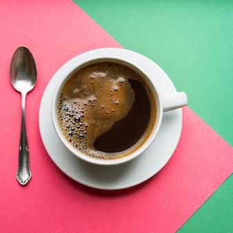 Черный кофе в белой чашке на фоне розовой и зеленой бумаги, вид сверху.