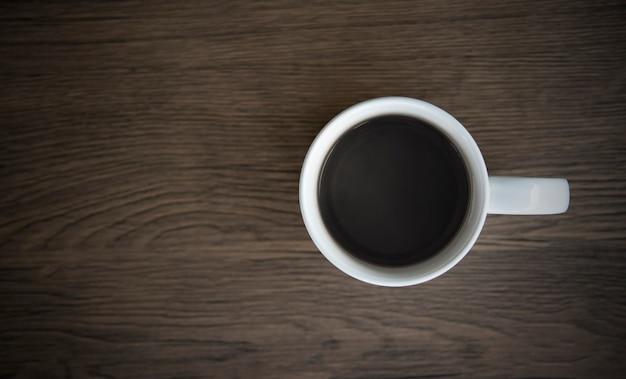 木製のテーブルの上の白いマグカップのブラックコーヒー。上面図