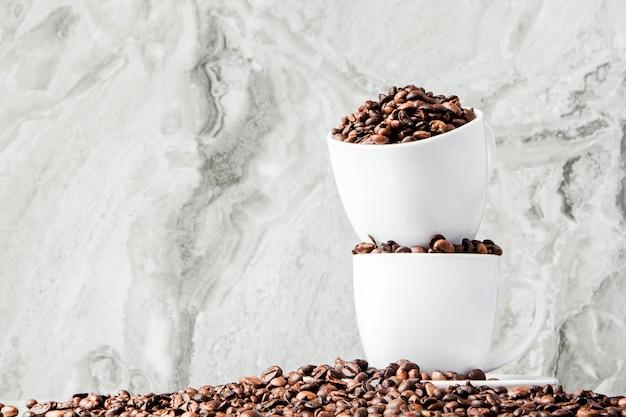 カップのブラックコーヒーと大理石の背景にコーヒー豆。上面図、テキスト用のスペース。