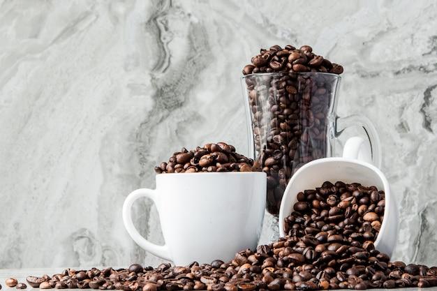 カップに入ったブラックコーヒーと大理石の壁にコーヒー豆。上面図、テキスト用のスペース。