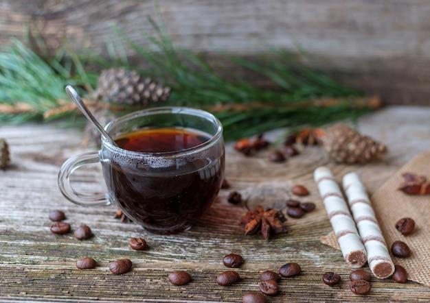 소나무 가지, 커피 콩, 아니스 별, 계피 및 웨이퍼 롤이있는 나무 테이블에 유리 컵에 블랙 커피