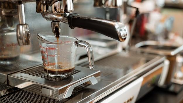 Черный кофе в мерной чашке на кофеварке