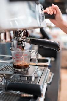 コーヒーメーカーに置く計量カップのブラックコーヒー