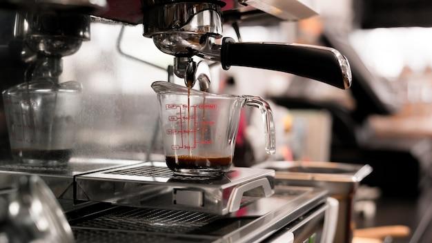 Черный кофе в мерной чашке надеть кофеварку