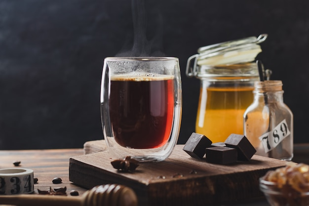 Черный кофе в стакане с паром над деревянной поверхностью, мед и темный шоколад