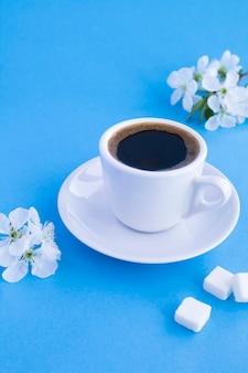 白いカップのブラックコーヒーと青いテーブルの開花木の枝。スペースをコピーします。