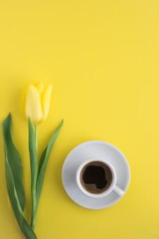 白いカップにブラックコーヒー、黄色に黄色いチューリップ1本