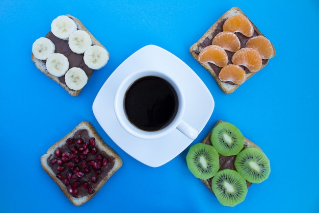 白いカップのブラックコーヒーと青い背景にチョコレートクリームとフルーツのサンドイッチ。