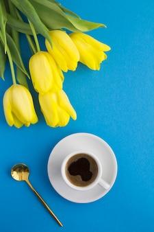 블루에 흰색 컵과 노란색 튤립에 블랙 커피