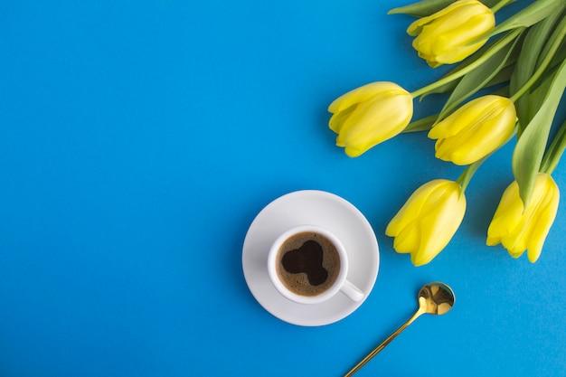 Черный кофе в белой чашке и желтые тюльпаны на синем
