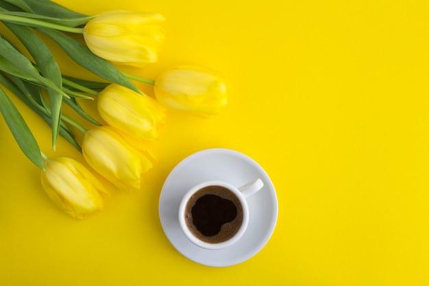 흰색 컵에 블랙 커피와 노란색에 노란색 튤립