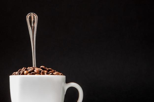 白いカップのブラックコーヒーと黒い壁のコーヒー豆。上面図、テキスト用のスペース。