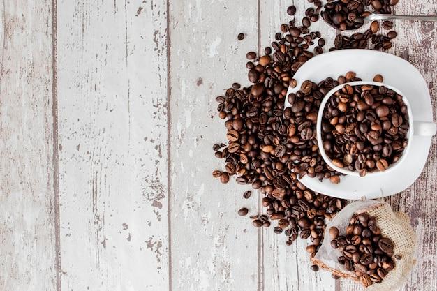 白いカップのブラックコーヒーと明るい木の壁のコーヒー豆。上面図、テキスト用のスペース。