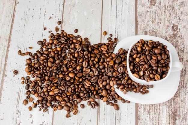 白いカップのブラックコーヒーとライトウッドのコーヒー豆