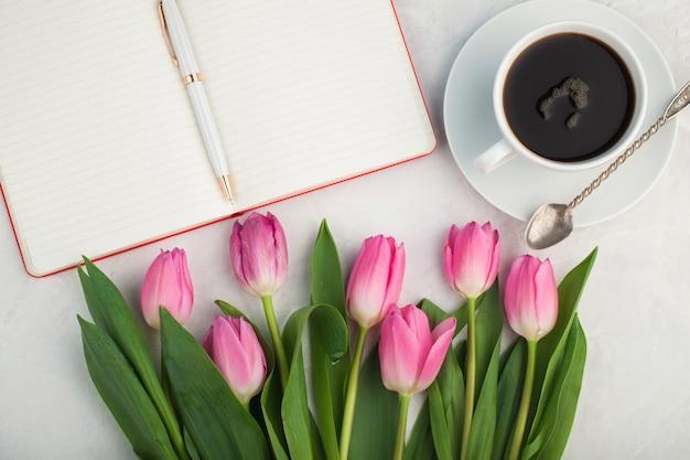 Черный кофе в белой чашке и тюльпаны.