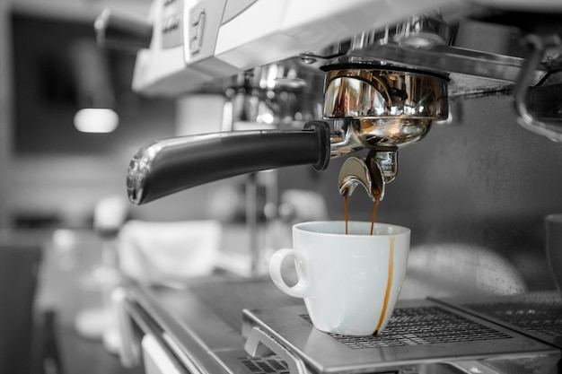 Черный кофе в белой чашке положить на кофеварку