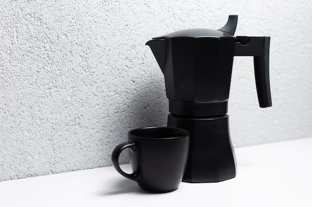 Черный кофейник мока и две чашки на белом.