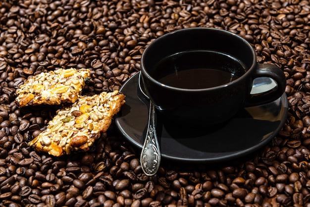 Кружка черного кофе и печенье на фоне кофейных зерен
