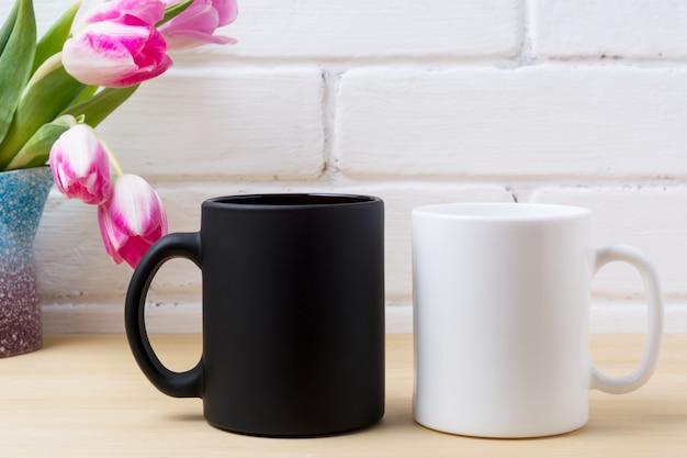 ピンクのチューリップとブラックコーヒーマグカップと白いカプチーノカップモックアップ