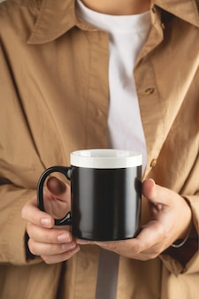 Макет черной кофейной кружки для демонстрации дизайна стильный макет чашки в женских руках