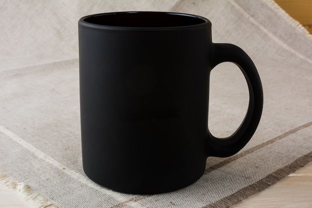 Black coffee mug mockup on the linen napkin