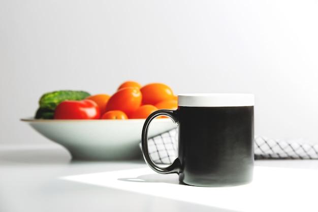 Макет черной кофейной кружки на кухонном столе, макет чашки для дизайна
