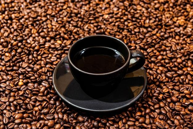 Кружка черного кофе на фоне кофейных зерен