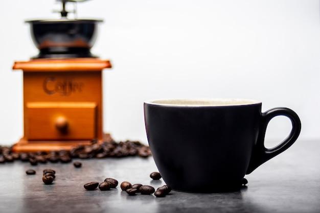 コーヒーグラインダーの背景の横にドロップされたコーヒー豆入りのブラックコーヒーマグ。
