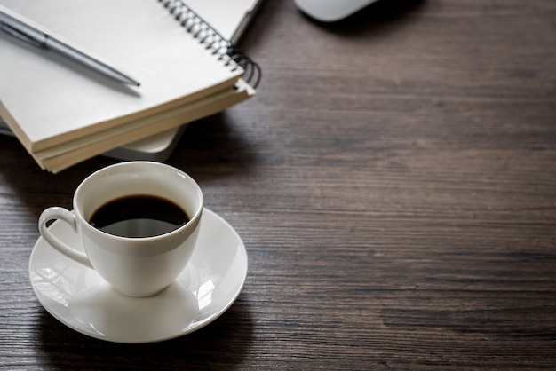 Black coffee on the office desk table with computer, silver pen