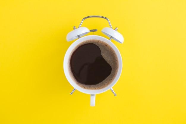 Черный кофе на циферблате белого будильника в центре желтого фона