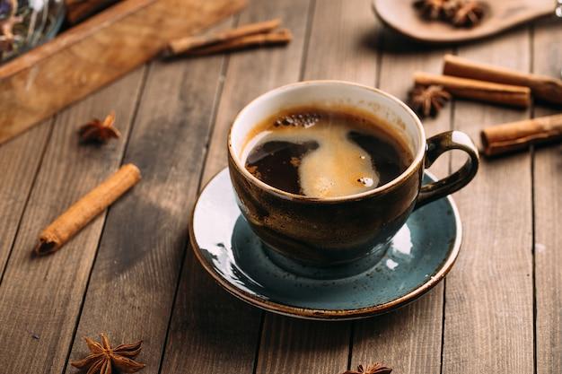 Черный кофе на деревянном столе, украшенном специями