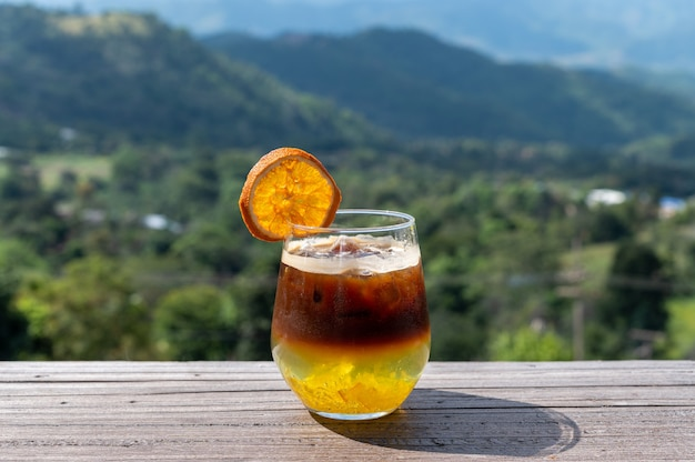 Black coffee orange mixed juice in glass with mountains view