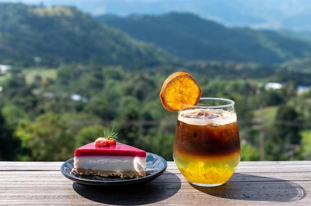 山の景色を望むガラスとストロベリーケーキのブラックコーヒーオレンジミックスジュース